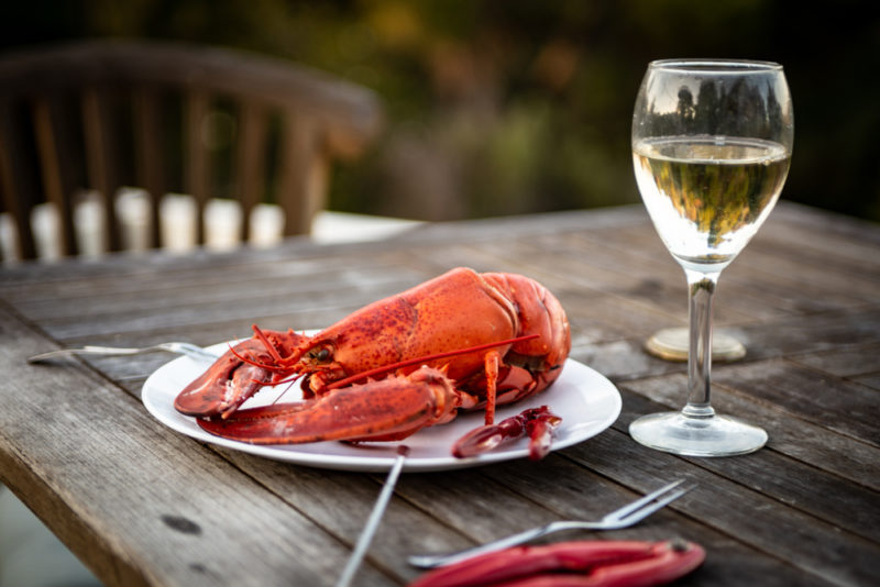 A fresh lobster on a table outside next to a glass of sauvignon blanc
