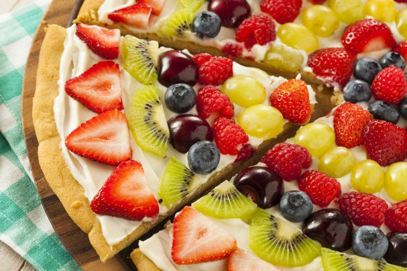 A fruit pizza with a white spread
