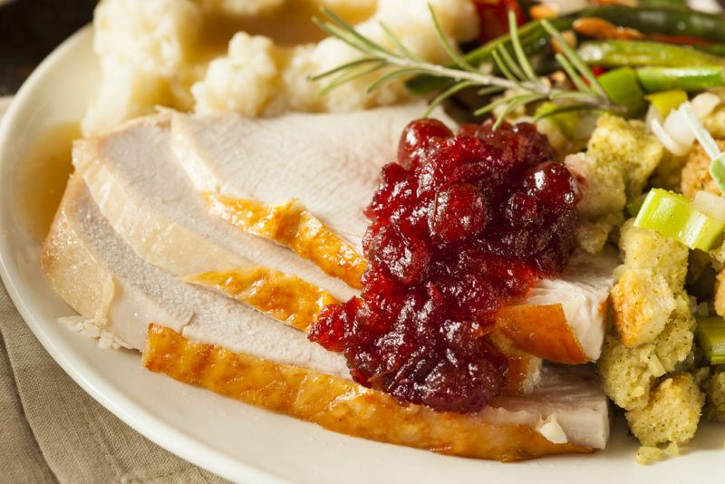 A white plate with a full turkey dinner, including stuffing, cranberry sauce, potatoes, and the turkey