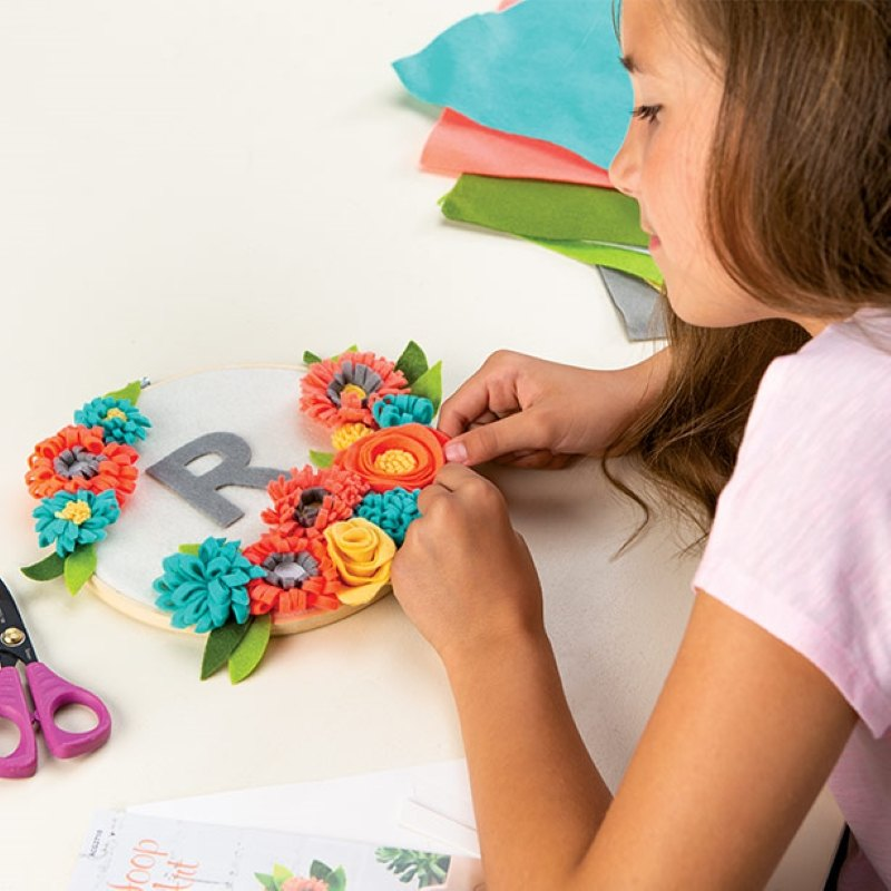 A girl at a table working on a craft attachinh fabric flowers to a circle with a felt R in the middle