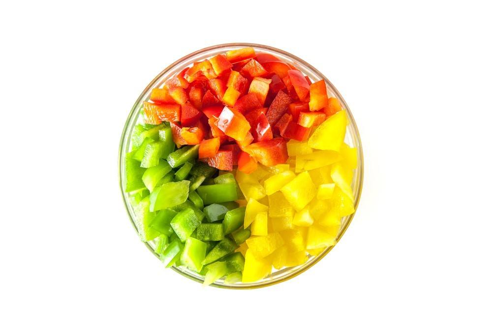 A glass bowl filled with three types of chopped bell peppers