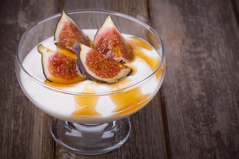 A glass dessert glass with Greek yogurt, figs, and honey
