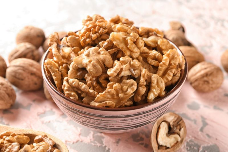 A ceramic or glass bowl that contains shelled walnuts, with whole walnuts on the table