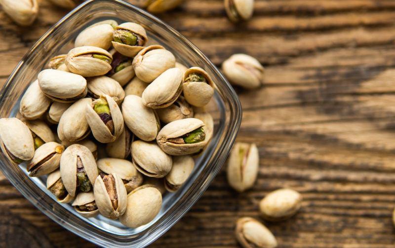 A glass jar with fresh pistachio nuts