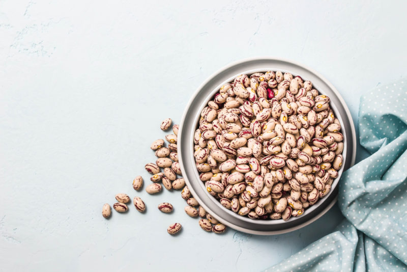 A glass jar of beans on a light background next to a blue cloth, with some of the beans on the table