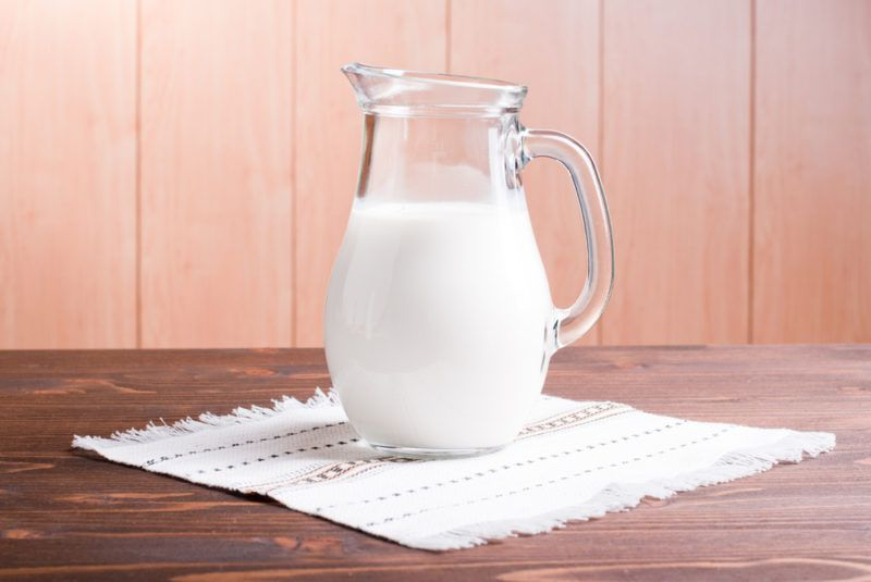 A glass jug of buttermilk on a wooden table with a cloth underneath it.