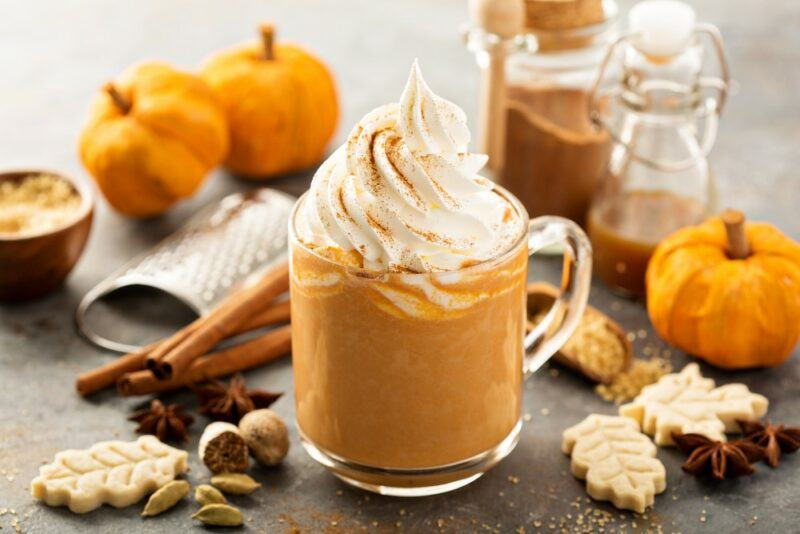 A glass mug containing a pumpkin spice latte with two fresh pumpkins in the background, cookies and other ingredients on the table