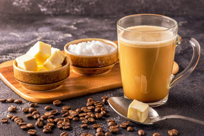 A wooden board with a small bowl of butter and one of coconut oil, next to a spoon of butter and a mug of Bulletproof coffee