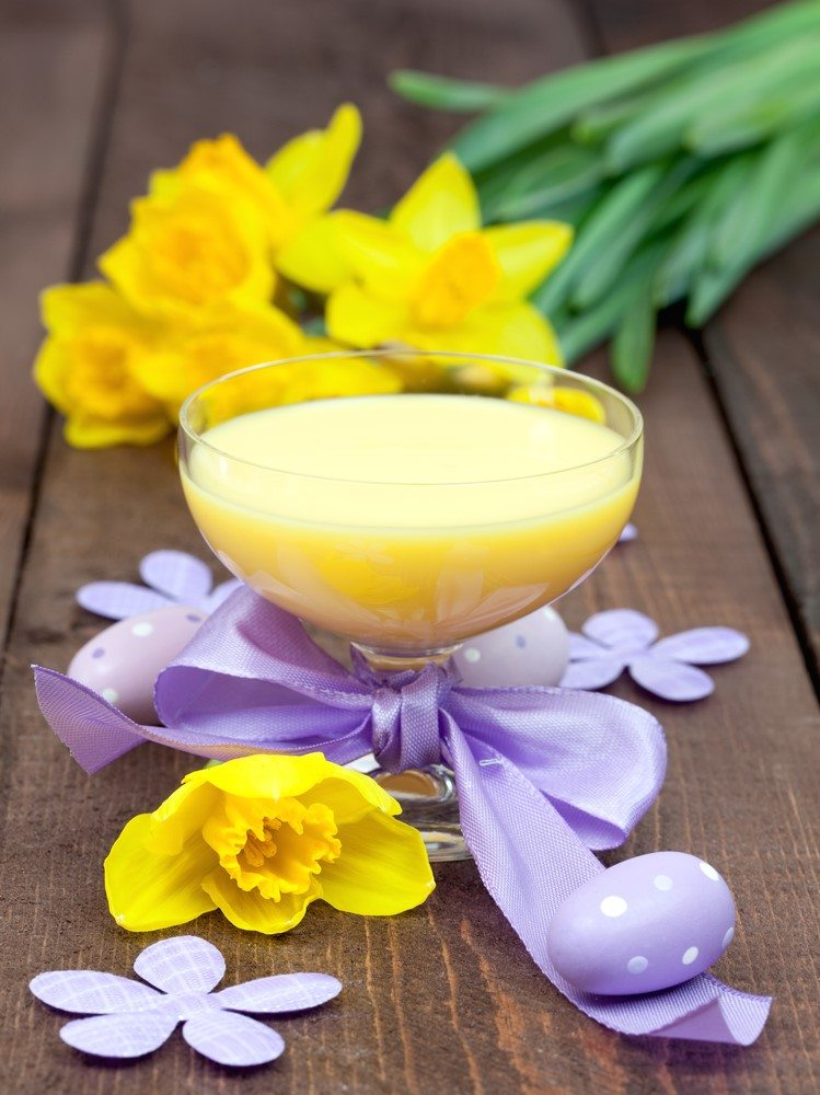 A wine glass of eggnog next to daffodils and a purple ribbon