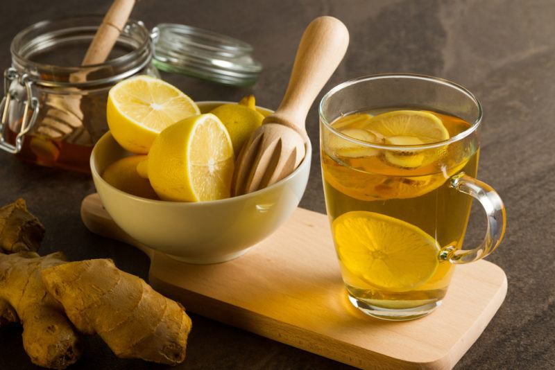 A white bowl of lemons, next to a jar of honey and a mug of hot lemon drink
