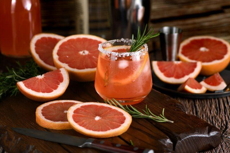 A glass of paloma cocktail on a table, with slices of grapefruit all around