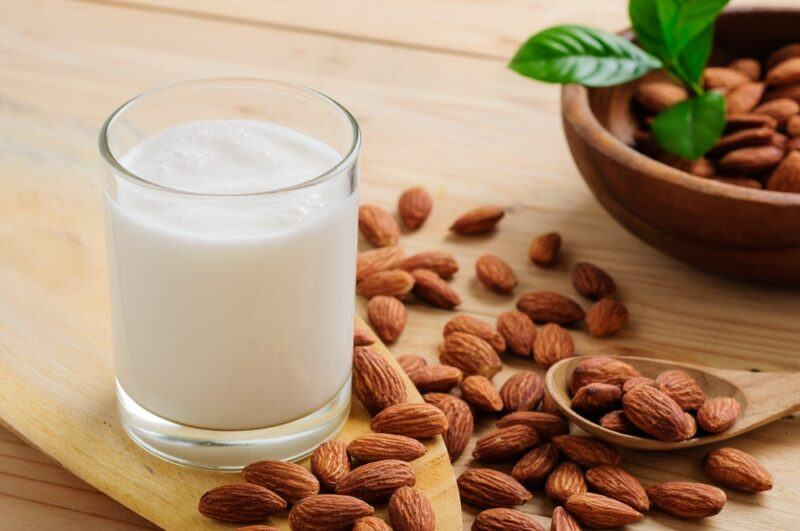 A glass of almond milk on a wooden board next to almonds and a bowl of almonds
