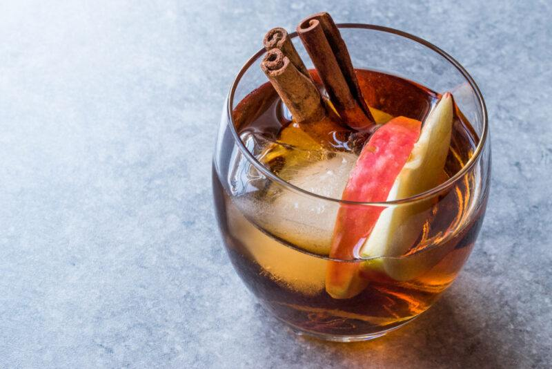 A glass of apple brandy with ice and cinnamon on a gray table