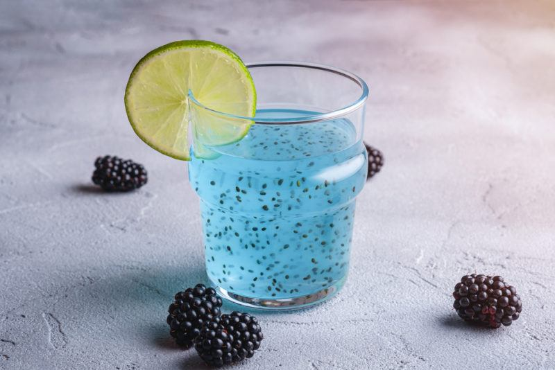 A glass containing a blue cocktail with chia seeds that has been garnished with lime. There are a few berries on the table