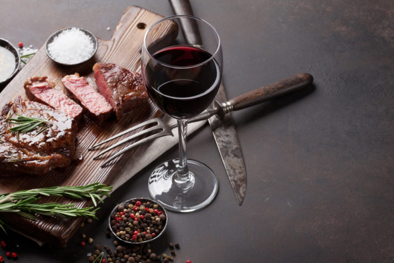 A gray table with a wooden board that contains various types of meat, next to red wine, a knife, and a fork
