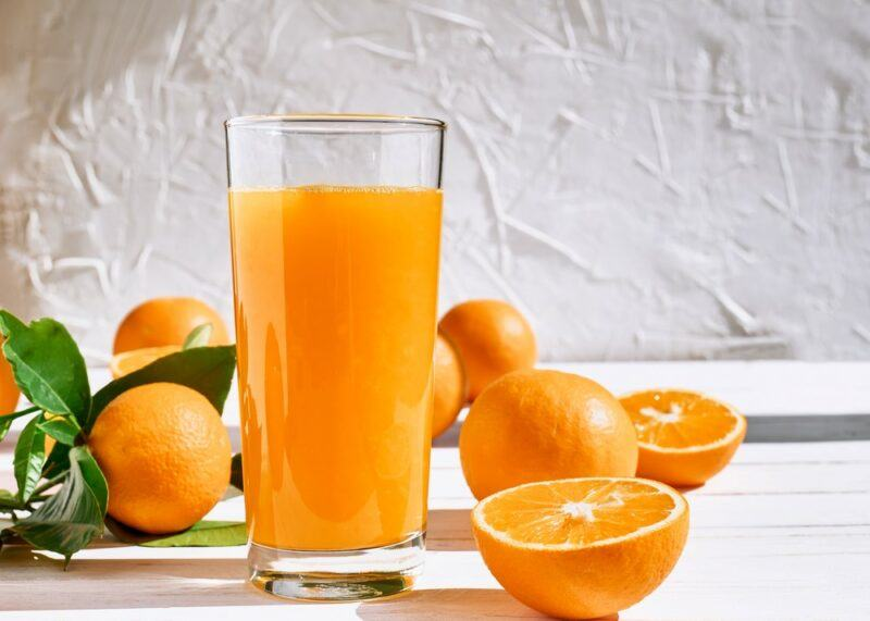A white table with a glass of dark colored orange juice and some orange halves