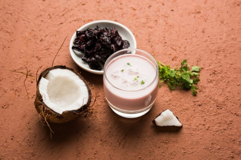 A glass of solkadhi next to a bowl of kokum fruit and half a coconut on a wooden table