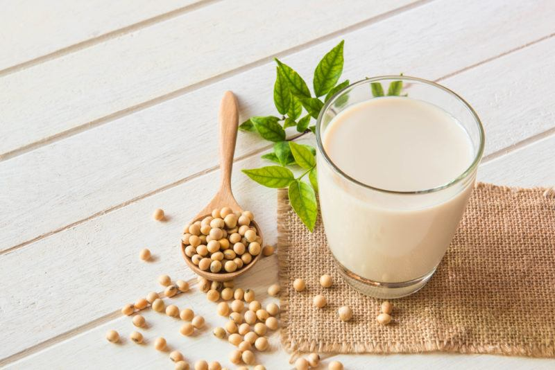 A glass of soy milk with a spoon of soybeans