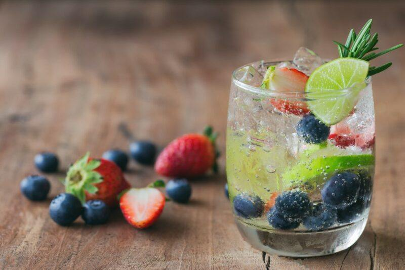 A glass of sparkling water with fresh fruit in it, plus fresh fruit next to it