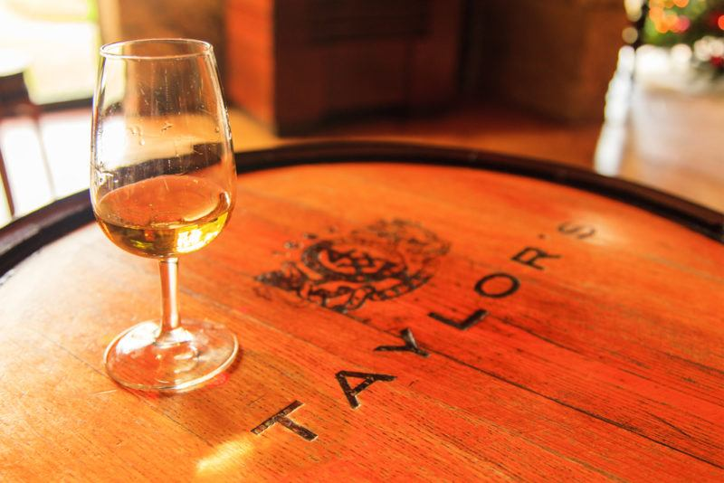 A large oak barrel with Taylor's written on top and a glass of tawny port