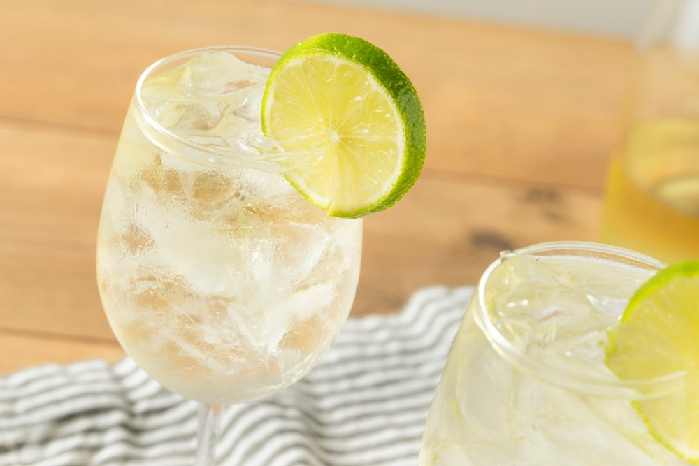 Two glasses of a white wine spritzer with a lime as a garnish