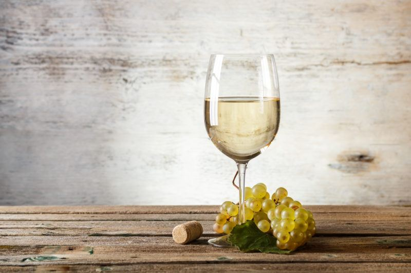 A glass of white wine on a table with some white grapes at the base