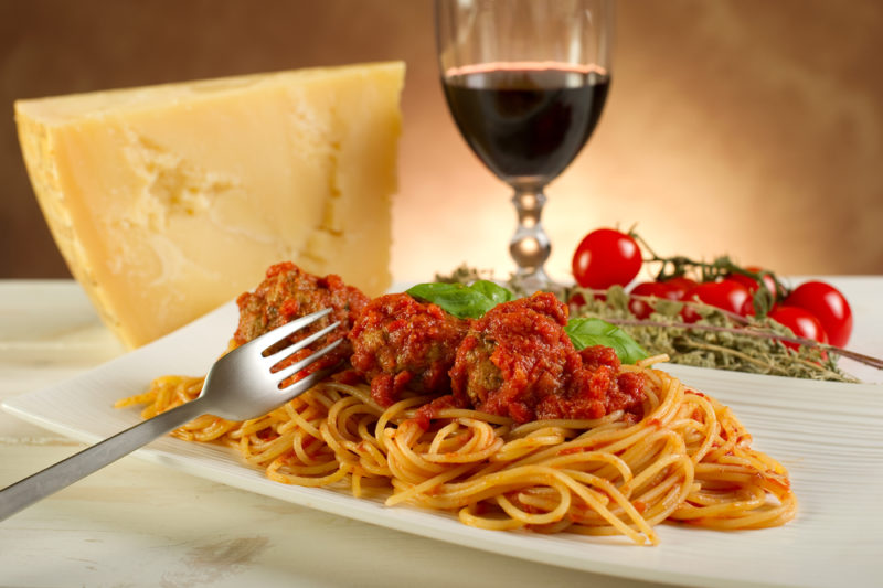 A white plate with spaghetti and meatballs, along with a block of cheese, a glass of red wine, and some tomatoes
