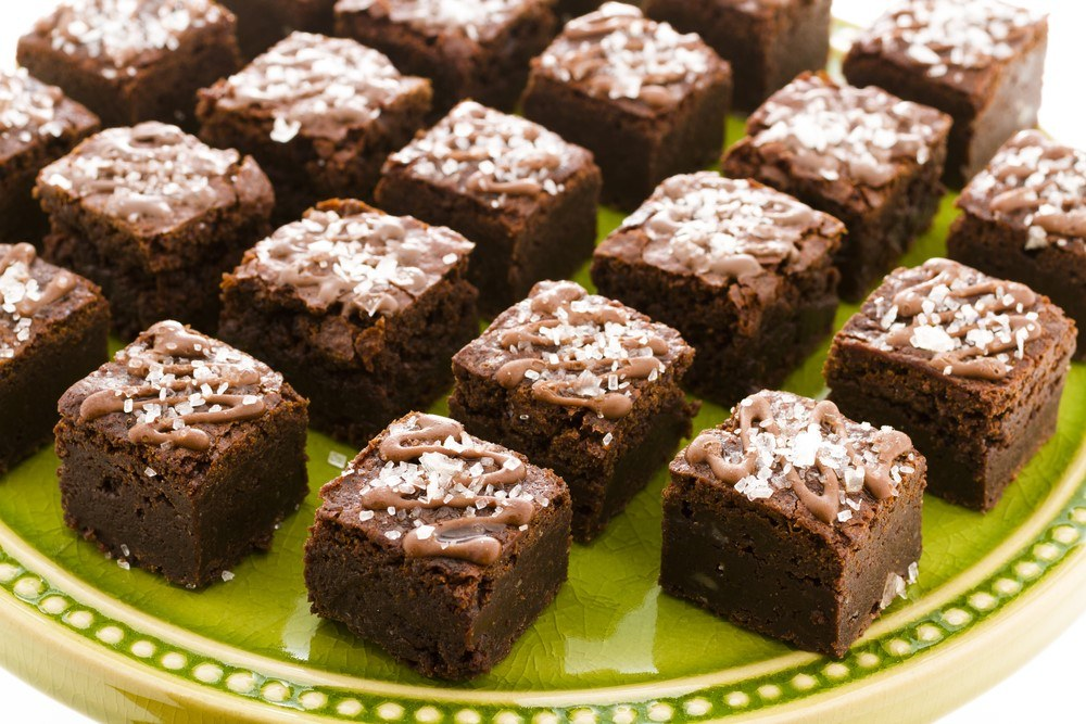 A lime green plate with small chocolate brownies shaped like squares