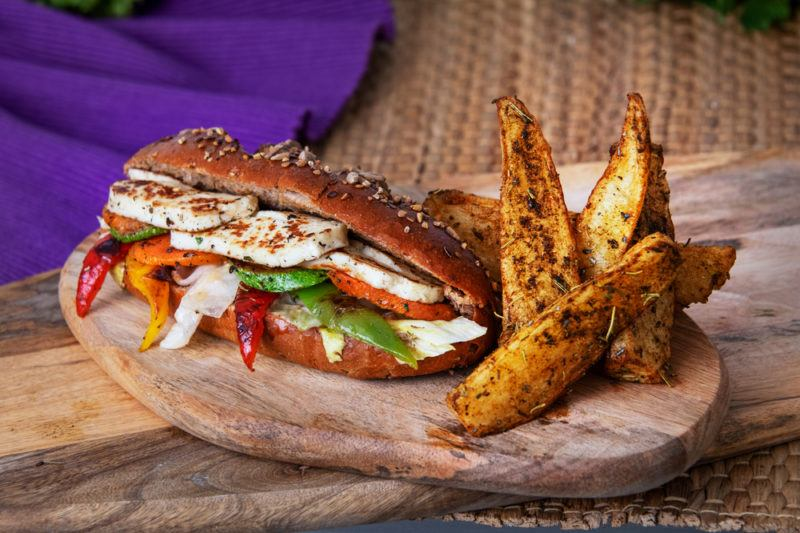 A wooden board on a wooden table, with a purple cloth in the background. On the board is a halloumi sandwich filled with grilled veggies, next to some potato wedges
