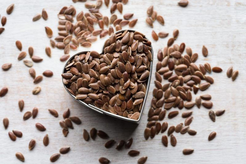 A heart shaped container of flaxseeds with more flaxeeds scattered on a table