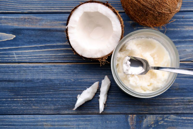 A top down image showing a jar of coconut oil with a spoon, next to a half coconut, a whole coconut, and some slivers on a blue table