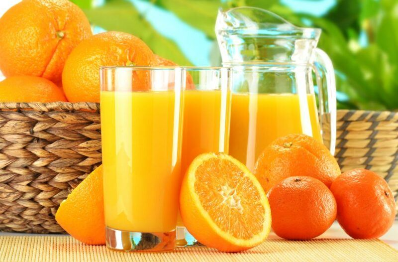 Two large glasses of orange juice and a jug of the juice, next to a basket of oranges and some oranges on the table