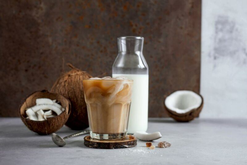 A bottle of coconut milk next to a coffee made with the milk and some coconuts