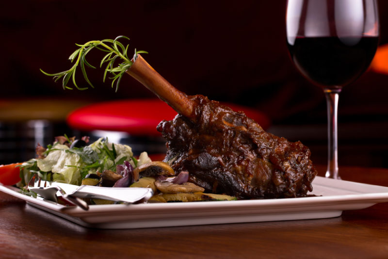 A white plate with a cooked lamb leg, ext to a glass of red wine