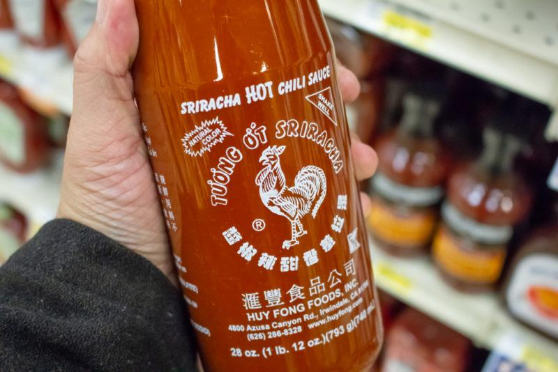 A large bottle of sriracha being held in a grocery store