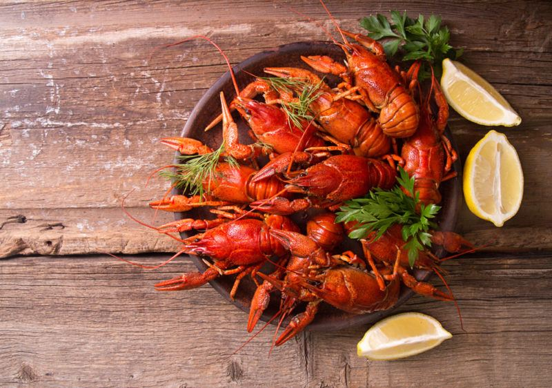 A dark bowl filled with crayfish, ready for a party, with a few lemon wedges just outside of it