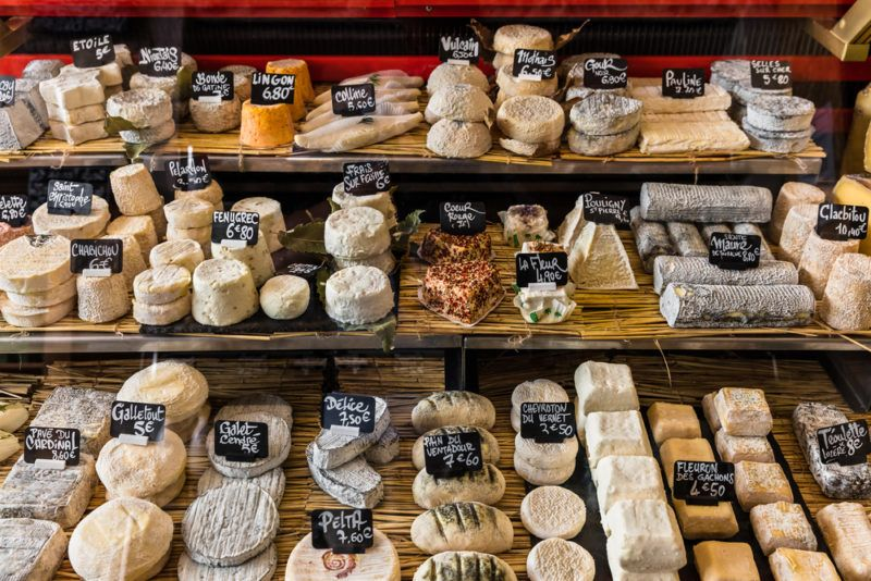 A large selection of different french and italian cheeses on the counter of a small store at the Aligre Market (Marche d'Aligre) in the Bastille district. Paris, France