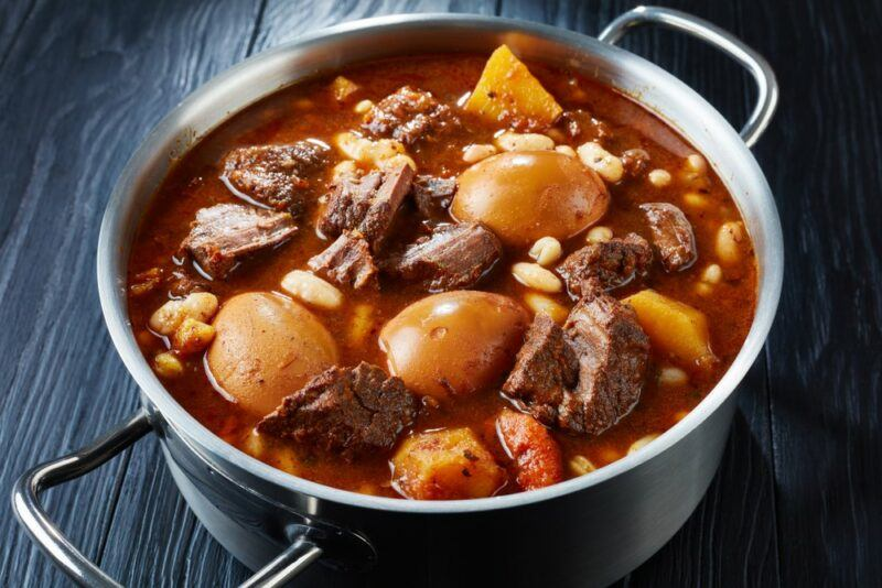 A large stainless steel pot containing a Jewish slow cooked dish called cholent. It can be made in many different ways.