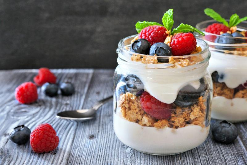 Two glass jars with layered parfaits that include cereal, yogurt and fruit