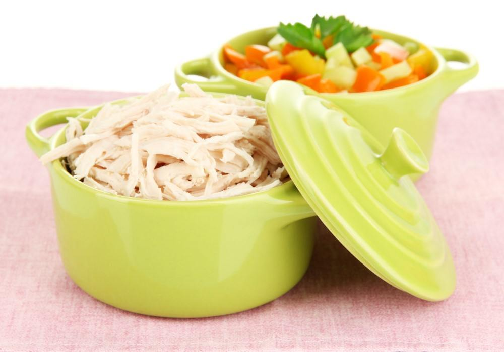 A lime bowl filled with shredded chicken, in front of another bowl of vegetables
