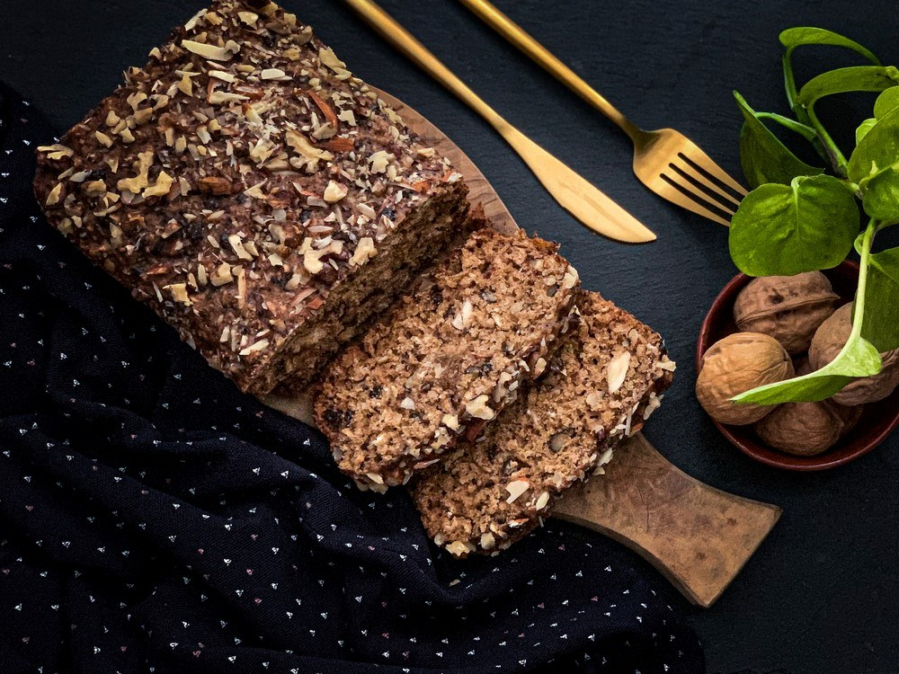 A wooden table with keto seed bread that has been cut into slices
