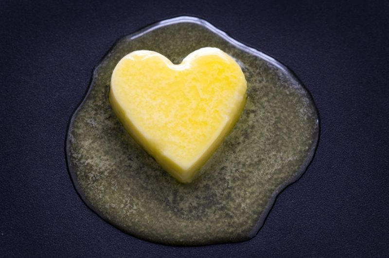 A pat of butter in the shape of a heart that's melting in a frypan