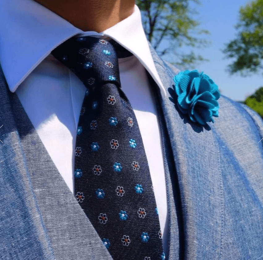 A man in a shirt tie and coat, the tie has tiny flowers with navy background and cloth boutonniere