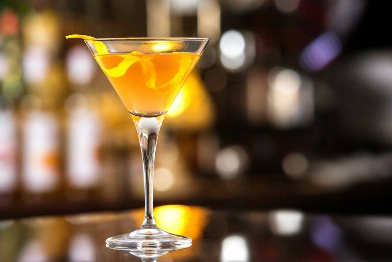A martini glass containing a Roosevelt cocktail with a twist of citrus
