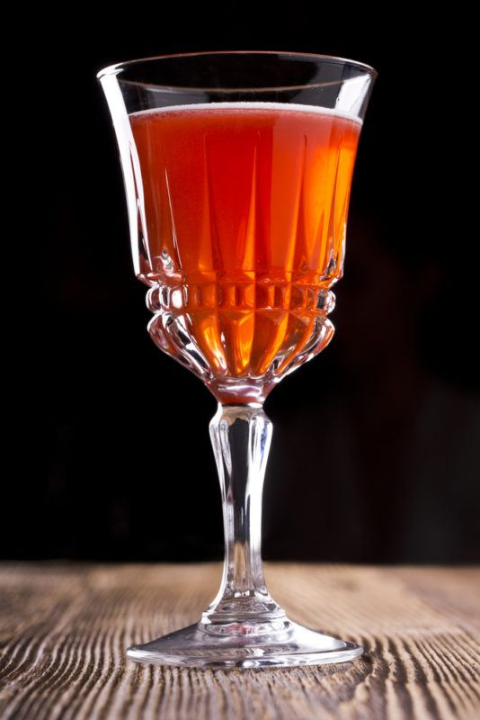 A millionaire cocktail in a crystal glass on a wooden table against a black background