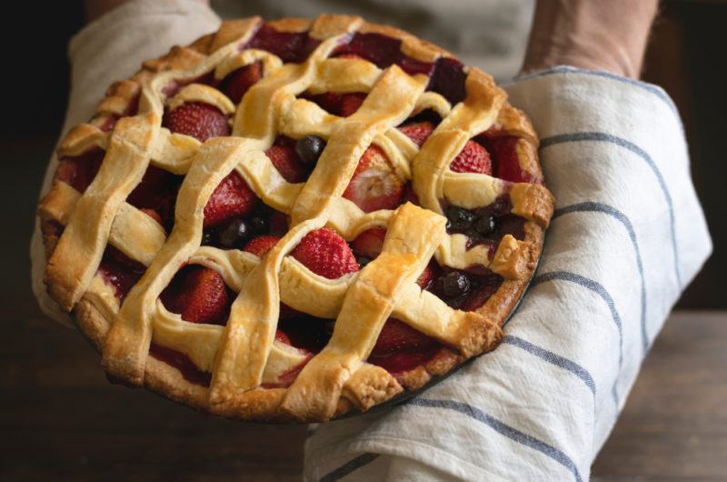 A mixed berry lattice pie being held on a striped tea towel