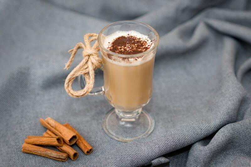 A glass mug of an eggnog latte with cinnamon sticks