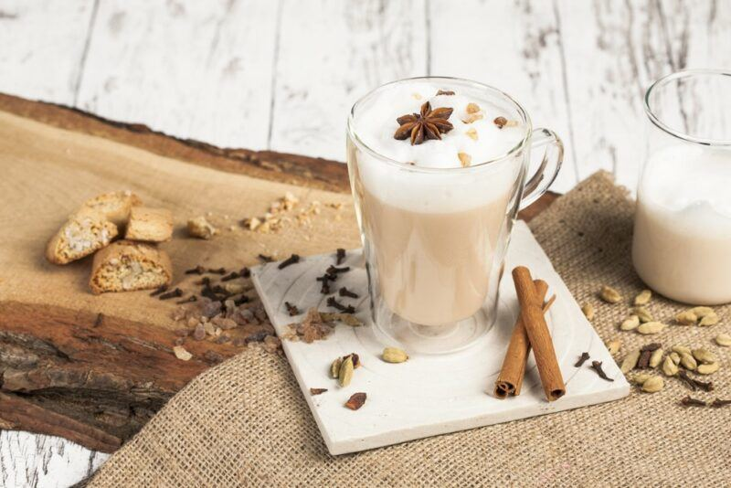 A glass mug of a chai latte on a white wooden table next to a piece of wood