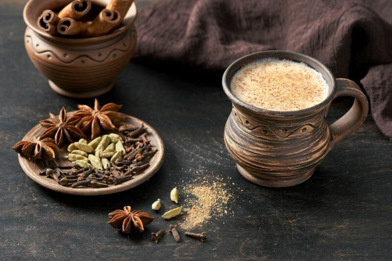 A clay mug of chai tea, next to a plate that contains all the spices used to make the tea