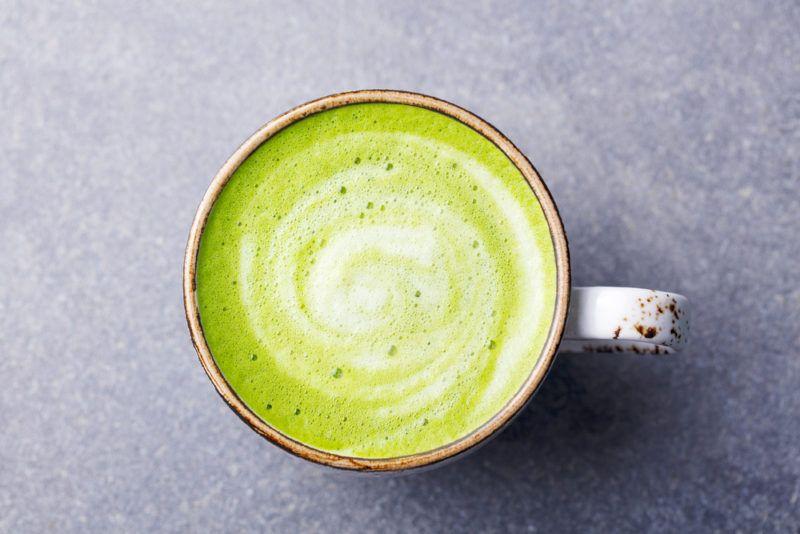 A mug of matcha latte on a gray bench top
